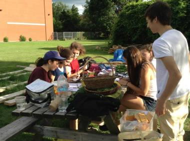 Students weighing the harvest, socializing and planning.